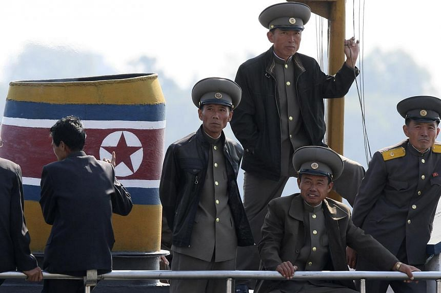 North Korean soldiers on a boat on the banks of the Yalu River, near the North Korean town of Sinuiju, on Oct 6, 2014. -- PHOTO: REUTERS