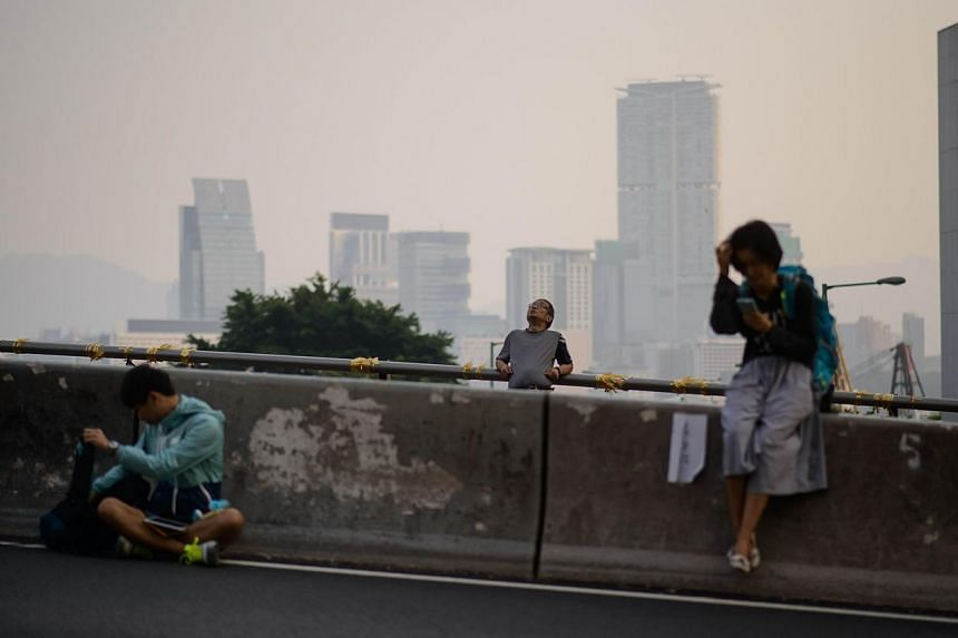 Pro-democracy protesters wake up following a night on an occupied road in the Admiralty district of Hong Kong early on Oct 8, 2014. -- PHOTO: AFP