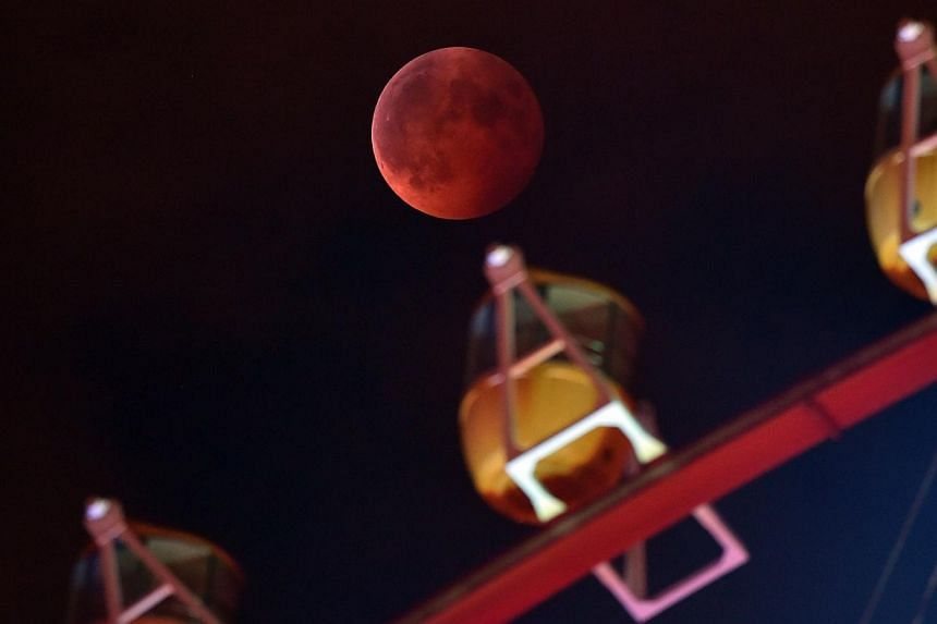 A total lunar eclipse is seen behind a ferris wheel in Tokyo, on October 8, 2014. -- PHOTO: AFP