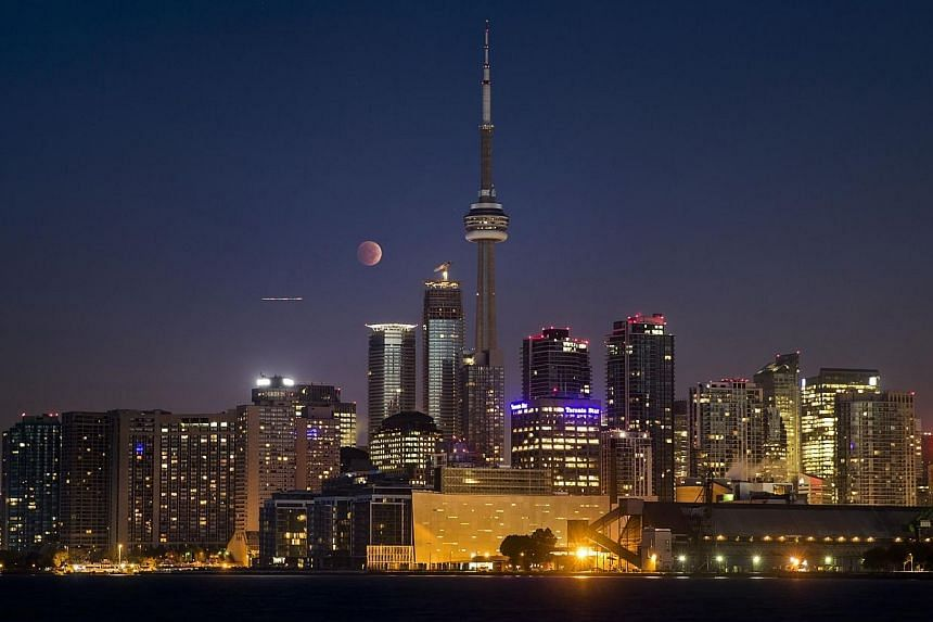 The moon turns orange during a total lunar eclipse behind the CN Tower and the skyline during moonset in Toronto on Oct 8, 2014. -- PHOTO: REUTERS