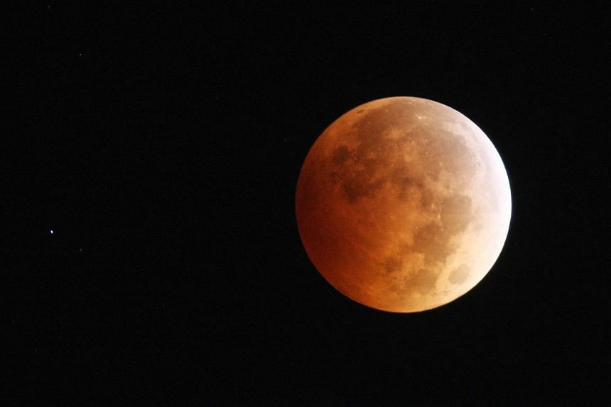 "The moon is illuminated by sunlight reflected off the Earth during a total lunar eclipse, one of four so-called ""blood moons"", on October 8, 2014 in Los Angeles, California. -- PHOTO: AFP"