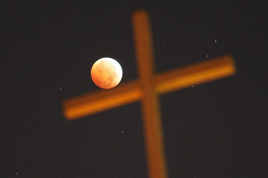 "A religious cross is seen as the moon is illuminated by sunlight reflected off the Earth during a total lunar eclipse, one of four so-called ""blood moons"", on Oct 8, 2014 in Los Angeles, California. -- PHOTO: AFP"