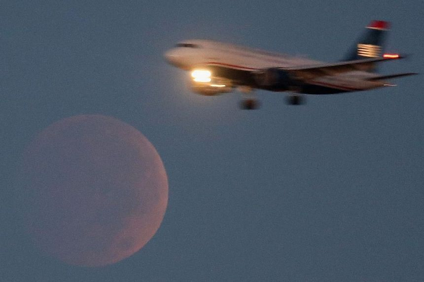 A commercial Airliner on approach to Reagan National Airport flies past the full moon during a lunar eclipse Oct 8, 2014 in Washington, DC. -- PHOTO: AFP
