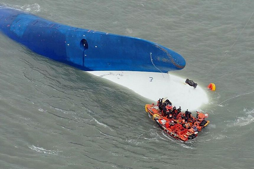 This aerial handout file photo by the South Korea Coast Guard taken at sea some 20 kilometres off the island of Byungpoong in Jindo on April 16, 2014, shows coast guard members searching for passengers near a South Korean ferry (centre) that capsized
