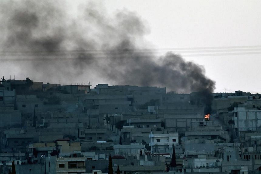 Smoke rises from the city centre of the Syrian town of Ain al-Arab, known as Kobane by the Kurds, as seen from the Turkish-Syrian border during heavy fighting, in the south-eastern town of Suruc, Sanliurfa province, on Oct 7, 2014.Militants fro