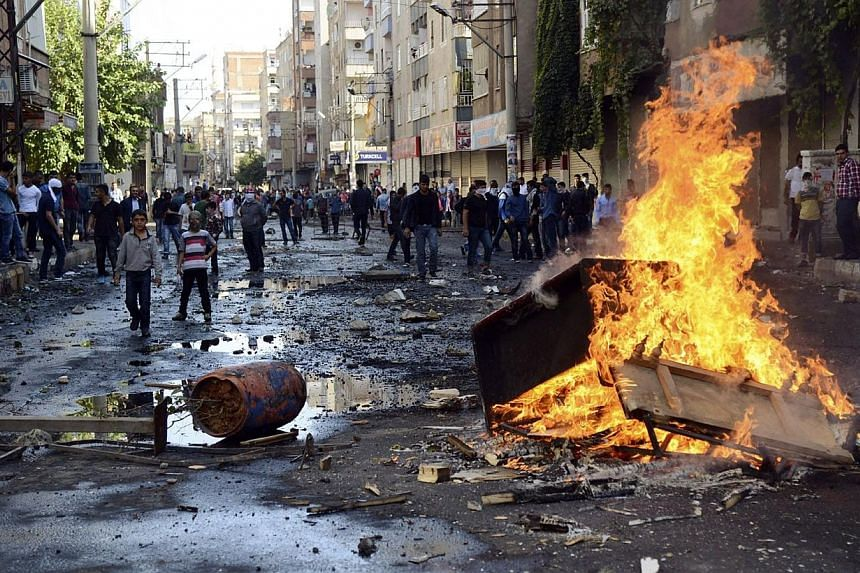Kurdish protesters set fire to a barricade set up to block the street as they clash with riot police in Diyarbakir on Oct 7, 2014.In a measure unprecedented in the last years, the Turkish army has deployed in the streets of the cities of Diyarb