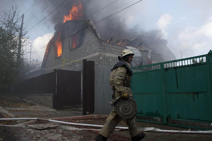 A firefighter attempts to extinguish a fire in houses hit by an Uragan missile in a north-western district in Donetsk on Oct 5, 2014. More than 330 people have been killed in Ukraine since a fragile truce began a month ago, with five million peo