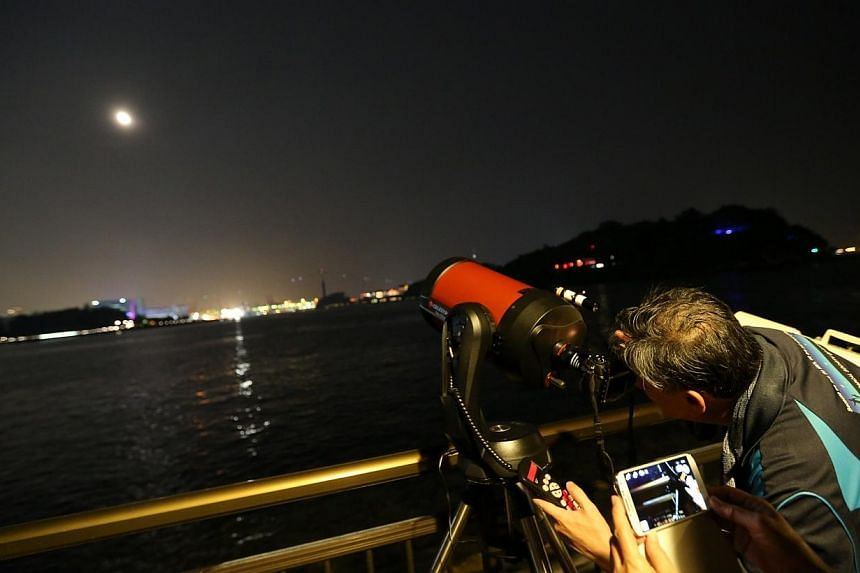 Mr Albert Lim from the Astronomical Society of Singapore (TASOS) taking pictures of the lunar eclipse through his telescope at Labrador Park. -- ST PHOTO: ONG WEE JIN