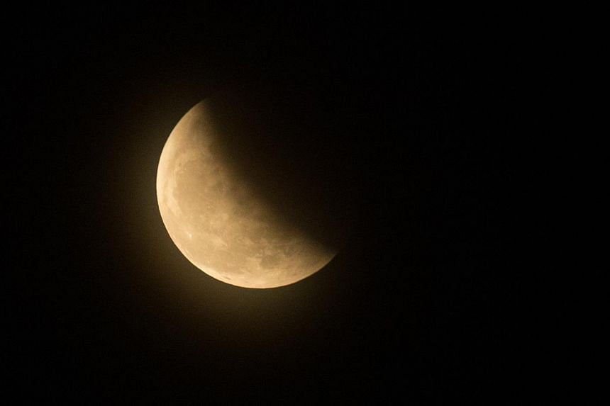 A hazy 'Blood red' moon, in partial eclipse, seen in Singapore from Labrador Park. -- ST PHOTO: ONG WEE JIN