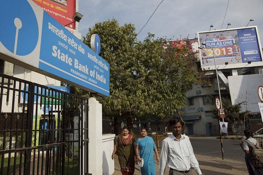 Pedestrians walk by a State Bank of India bank branch in Mumbai, India on Wednesday, Jan 16, 2013. Singapore granted qualifying full bank privileges to three Indian banks. Two have been approved so far: the State Bank of India and ICICI Bank. -- PHOT