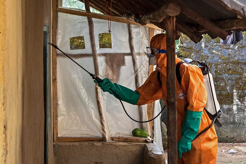 A volunteer in protective suit sprays disinfectant outside a home in Waterloo, Sierra Leone, on Oct 7, 2014, prior to taking away the body of a woman who died of Ebola.The epidemic could deal a US$32.6 billion (S$41 billion) blow to the West Af
