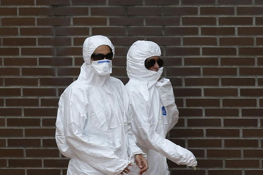 Workers in protective clothing head towards the entrance of the apartment building of a nurse who contracted Ebola, in Alcorcon, outside Madrid on Oct 8, 2014. A Spanish nurse may have become infected with Ebola when she touched her face with a