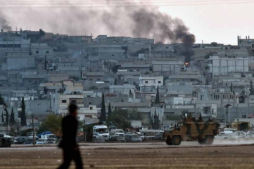 Smoke rises from the city centre of the Syrian town of Ain al-Arab, known as Kobane by the Kurds, as seen from the Turkish-Syrian border during heavy fighting, in the southeastern town of Suruc, Sanliurfa province on Oct 7, 2014.-- PHOTO: AFP