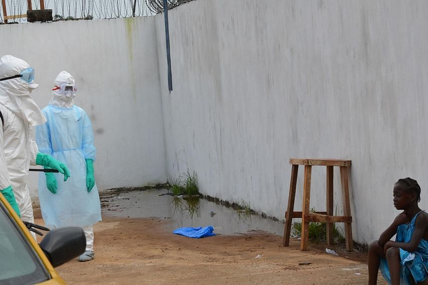 """A girl cries outside the """"Island Clinic"""", a new Ebola treatment centre that opened in Monrovia after the death of her parents by the disease on Sept 23, 2014. -- PHOTO: AFP"""