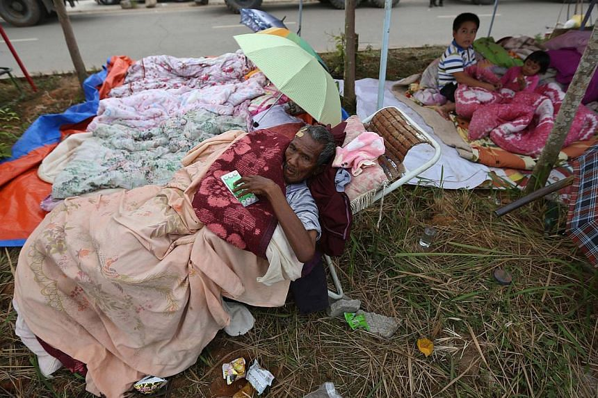 An injured man rests by the roadside in Yongping township after a 6.4 magnitude earthquake hit Jinggu county, Yunnan province, on Oct 8, 2014. -- PHOTO: REUTERS