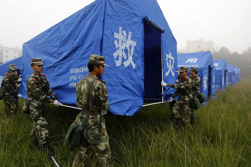 Paramilitary policemen set up a relief tent in Yongping township after an earthquake hit Jinggu county, Yunnan province, on Oct 8, 2014. -- PHOTO: REUTERS