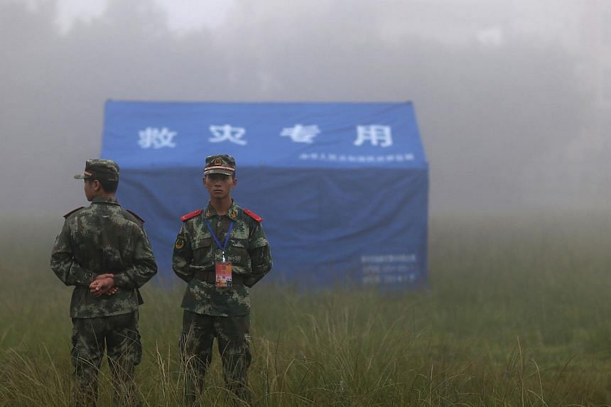 Paramilitary policemen stand guard next to a relief tent in Yongping township after a 6.4 magnitude earthquake hit Jinggu county, Yunnan province, on Oct 8, 2014. -- PHOTO: REUTERS