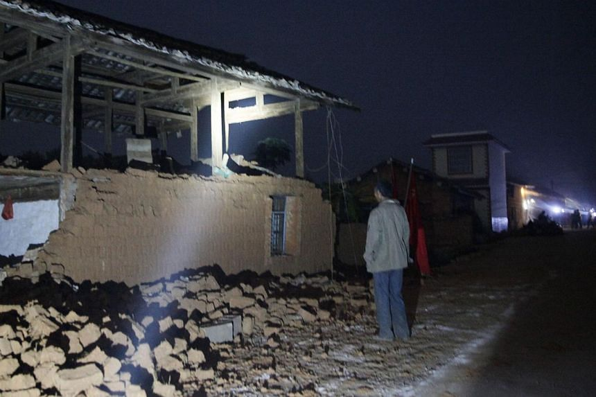 A man walks by damaged houses in Yongping, south-western China's Yunnan province on early Oct 8, 2014, after a shallow 6.0 magnitude earthquake hit the region close to China's border with Myanmar and Laos. -- PHOTO: AFP