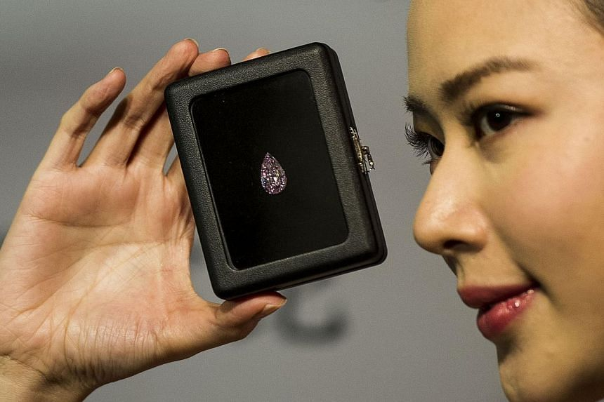 A model showcases a 8.41 carat pear-shape internally flawless fancy vivid pink diamond at a Sotheby's gallery in Hong Kong on Sep 18, 2014. -- PHOTO: AFP