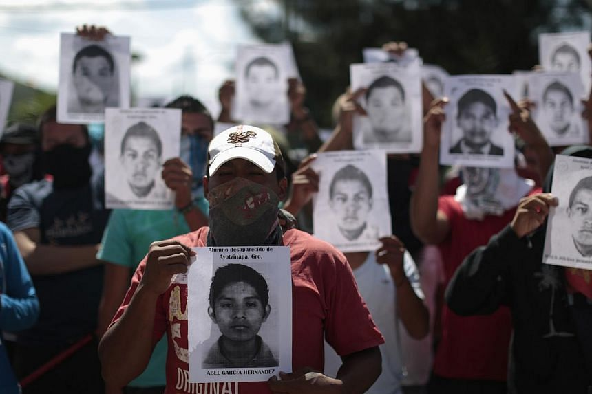 Students from Ayotzinapa Teacher Training College Raul Isidro Burgos hold pictures of missing students outside the General Attorney building in Chilpancingo, in Guerrero, on Oct 7, 2014.Mexico came under growing international pressure on Tuesda