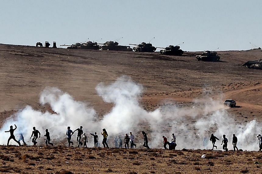 Kurdish people throw stones at Turkish armoured vehicles firing tear gas as Turkish army soldiers try to remove people from the Turkish-Syrian border area near the Syrian town of Ain al-Arab, known as Kobane by the Kurds, in the southeastern town of