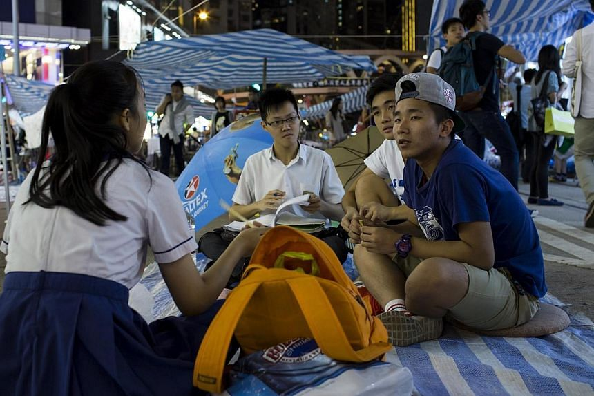Secondary school students do their homework at a protest site, as protesters occupy a main road at Causeway Bay shopping district, in Hong Kong on Oct 8, 2014. -- PHOTO: REUTERS