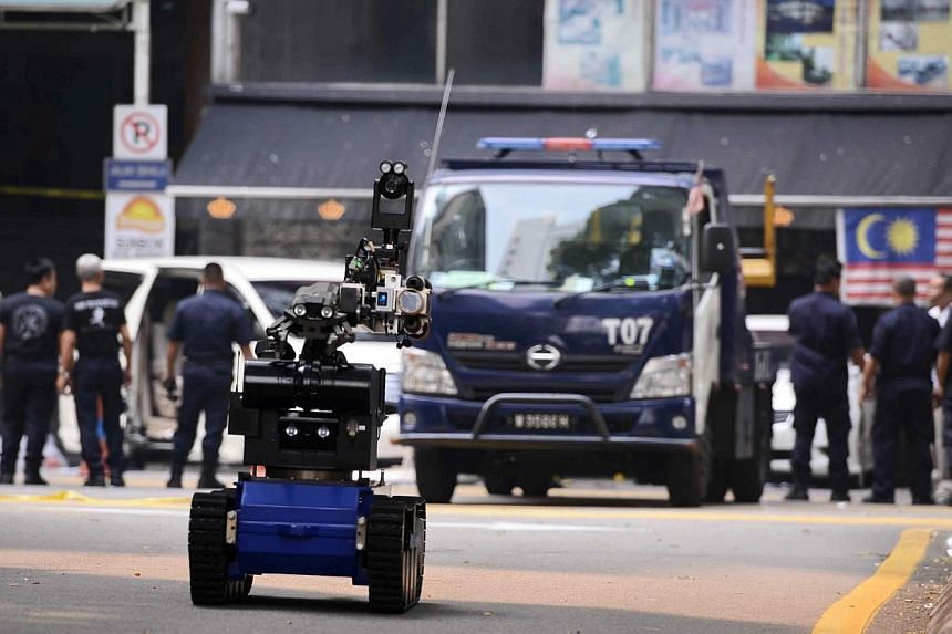A bomb disposal robot (front) is deployed after a grenade exploded in front of the Sun Complex in Jalan Bukit Bintang, Kuala Lumpur on Oct 9, 2014. -- PHOTO: AFP