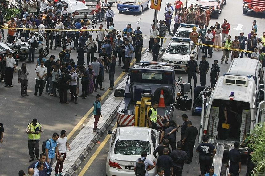People watch as police tow away a damaged white sedan (centre in foreground) at the scene of a grenade attack outside a shopping centre at Bukit Bintang in Kuala Lumpur on Oct9, 2014.An explosion outside a Kuala Lumpur pub on Thursday tha