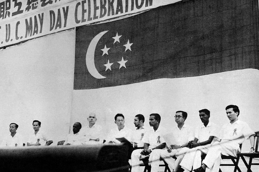 Prime Minister Lee Kuan Yew and the Minister for Health and Law K. M. Byrne (then Minister for Labour and Law) sit on the platform at the 1961 May Day Rally, flanked by leaders of former T.U.C. Communist machinations then split the trade unions into