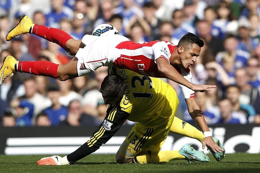 Arsenal's Chilean striker Alexis Sanchez (top) collides with Chelsea's Belgian goalkeeper Thibaut Courtois during the English Premier League football match between Chelsea and Arsenal at Stamford Bridge in London on Oct 5, 2014. Chelsea observed