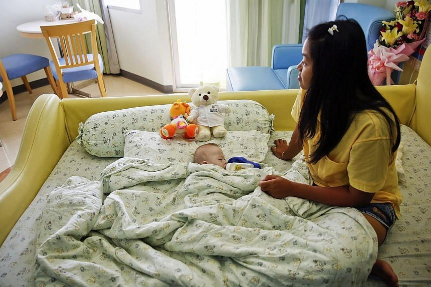 Gammy, a baby born with Down's Syndrome, is fed by his surrogate mother Pattaramon Janbua at a hospital in Chonburi province on Aug 3, 2014. -- PHOTO: REUTERS