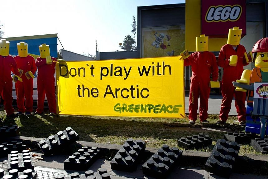 Greenpeace activists hang a banner on July 24, 2014 in front LEGO headquarters in Santiago, Chile.The world's largest toymaker Lego said on Thursday it was ending a deal with oil giant Shell, bowing to pressure from a Greenpeace campaign linkin