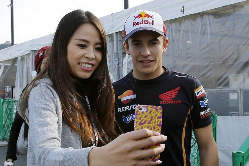 Honda MotoGP rider Marc Marquez (right) of Spain poses for a photo with a fan in the paddock area at the Twin Ring Motegi circuit ahead of Sunday's Japanese Grand Prix in Motegi, north of Tokyo on Oct 9, 2014.Marquez can retain his MotoGP title