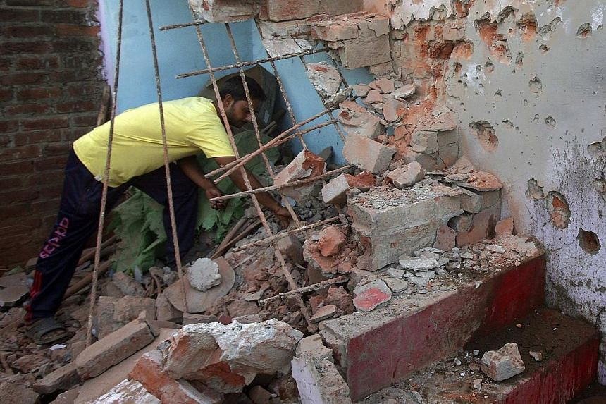 An Indian villager clears the debris from his house, which locals said was damaged by firing from the Pakistan side of the border, at Trewa village near Jammu on Oct 7, 2014.India's defence minister accused Pakistan on Thursday of making unprov