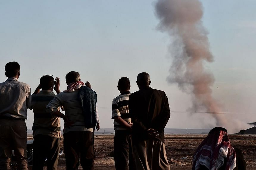 People watch smoke rising from the Syrian town of Ain al-Arab, known as Kobane by the Kurds, after an air strike, on Oct 8, 2014 in the Turkish-Syrian border, in the south-eastern village of Mursitpinar, Sanliurfa province. -- PHOTO: AFP