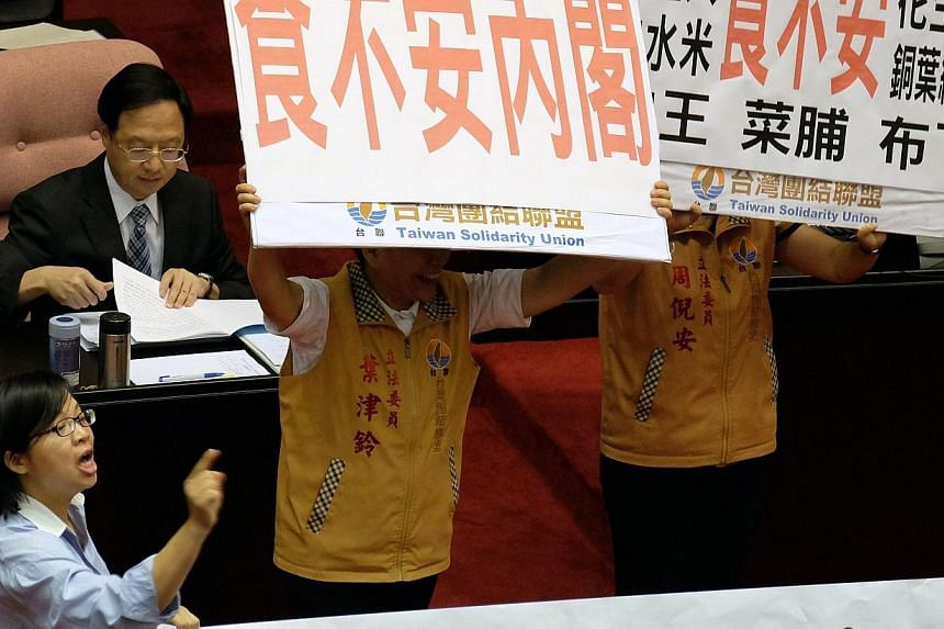 Opposition lawmakers display placards demanding Premier Jiang Yih-hua (left) apologise for the gutter oil scandal before his speech during the new parliament session in Taipei on Sept 12, 2014.The head of a leading Taiwanese food company resign