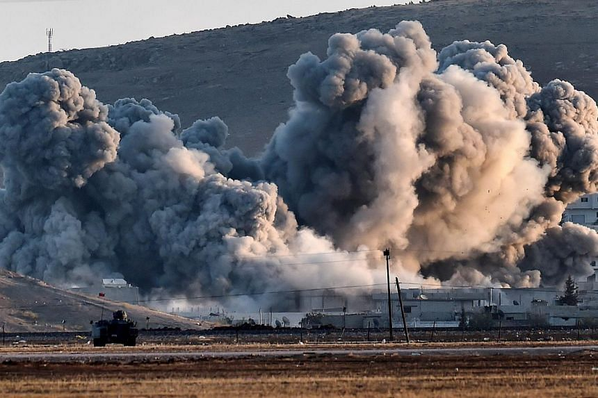 Smoke rises during airstrikes on the Syrian town of Ain al-Arab, known as Kobane by the Kurds, seen from the Turkish-Syrian border in the southeastern village of Mursitpinar, Sanliurfa province, on Oct 8, 2014. -- PHOTO: AFP