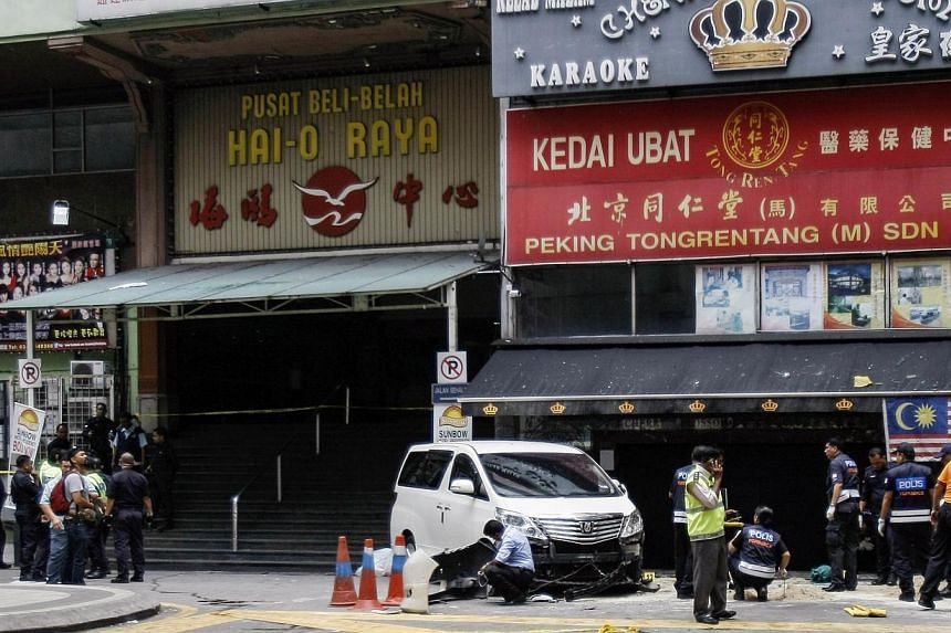 Police work at the scene of a grenade attack outside a shopping centre at Bukit Bintang in Kuala Lumpur on Oct 9, 2014. -- PHOTO: REUTERS