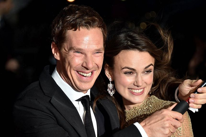 British actors Keira Knightley (right) and Benedict Cumberbatch brave the weather as they pose for pictures during the BFI London Film Festival's premiere of 'The Imitation Game at the Odeon Leicester Square in central London on Oct 8, 2014. -- PHOTO