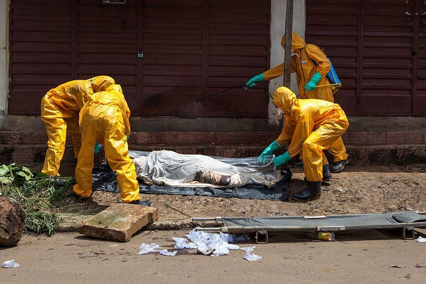 Volunteers pick up bodies of people who died of the Ebola virus on Oct 8, 2014 in Freetown, Sierra Leone.The United States will begin screening passengers arriving at US airports from West Africa for fever starting this weekend, US officials sa