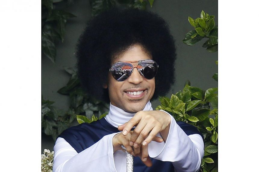 A file photo taken on June 2, 2014 shows US singer Prince attending the French Open tennis tournament. The rock and R&B veteran scored two new debuts in the top 10 in the United States, as two country music artists Blake Shelton and Lady Antebell