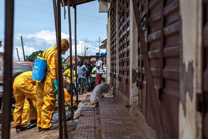 Volunteers look for bodies of people who died of the Ebola virus on Oct 8, 2014, in Freetown, Sierra Leone. -- PHOTO: AFP