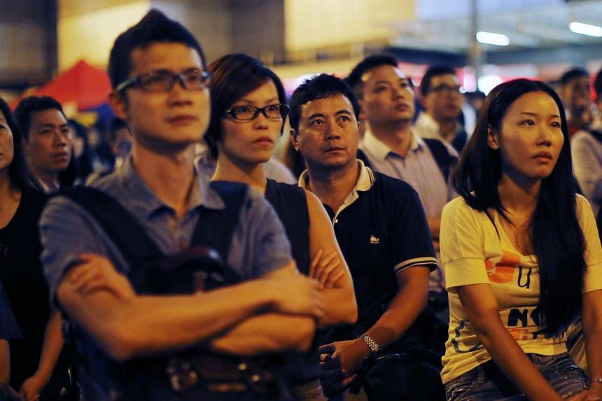 Demonstrators react during a speech after the government cancelled the talks scheduled for Friday as protesters block areas around the government headquarters office in Hong Kong on Oct 9, 2014. -- PHOTO: REUTERS