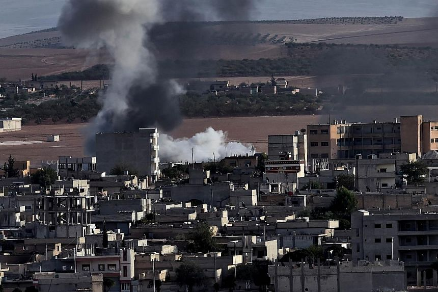 Smoke rises after an airstrike from the Syrian town of Ain al-Arab, known as Kobane by the Kurds, as seen from the southeastern Turkish village of Mursitpinar, Sanliurfa province, on Oct 9, 2014. -- PHOTO: AFP