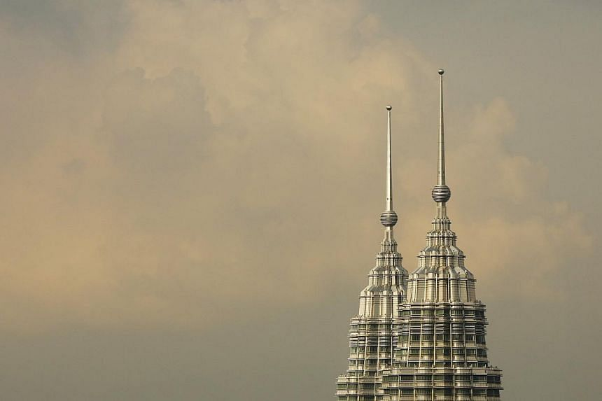 The peaks of the Petronas Twin Towers is seen in central Kuala Lumpur, on Aug 16, 2014.Malaysia sees economic growth holding steady at 5.0 to 6.0 per cent in 2015, despite expectations that domestic demand will be dampened by reduced fuel subsi