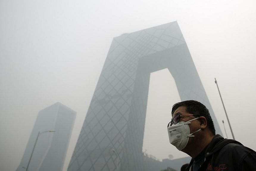 A man wearing a mask walks on a street during a hazy day in Beijing on Oct 10, 2014.Days of heavy smog shrouding swathes of northern China pushed pollution to more than 20 times recommended limits on Friday, despite government promises to tackl