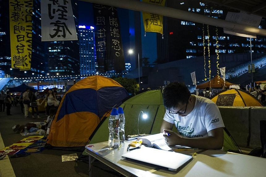 Pro democracy protester does his homework at Admiralty district during the rally after government called off the talks with students on Oct 10, 2014 in Hong Kong. -- PHOTO: AFP