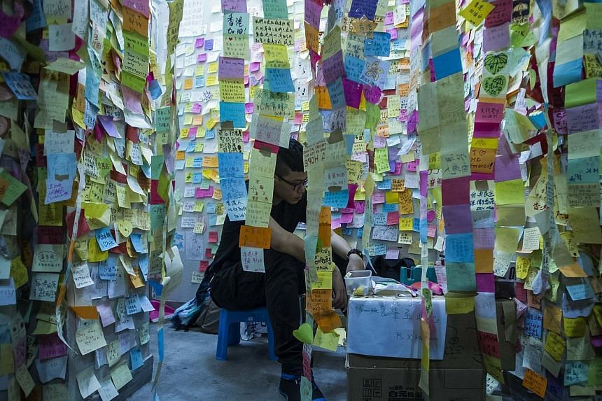 Pro democracy protester is seen surrounded by post it with encouragement at Admiralty district during the rally after government called off the talks with students on Oct 10, 2014 in Hong Kong. -- PHOTO: AFP