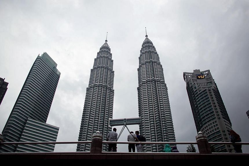 The Petronas Towers, center, stand in the central business district in Kuala Lumpur, Malaysia. Malaysian Prime Minister Najib Razak tabled the 2015 Budget on Friday, promising people-centric policies and a stronger economy. -- PHOTO: BLOOMBERG