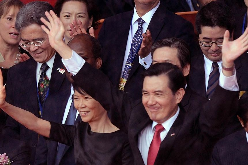 """Taiwan President Ma Ying-jeou (centre, right) and his wife Chow Mei-ching wave during the national day anniversary in front of the Presidential Palace in Taipei on Oct 10, 2014. Mr Ma on Friday called on Beijing to """"let some people go democratic firs"""